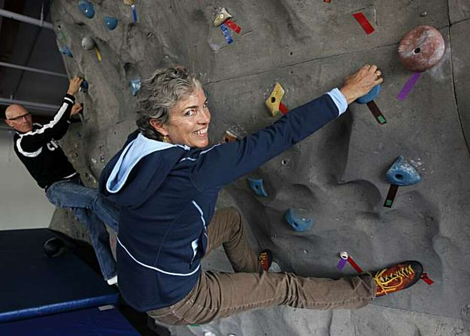 Clif Bar founder Gary Erickson (left) and his wife, co-owner Kit Crawford, cling to the climbing wall installed in the fitness center at their company's new corporate headquarters in Emeryville, Calif., on Thursday, Oct. 28, 2010. Photo: Paul Chinn, The Chronicle