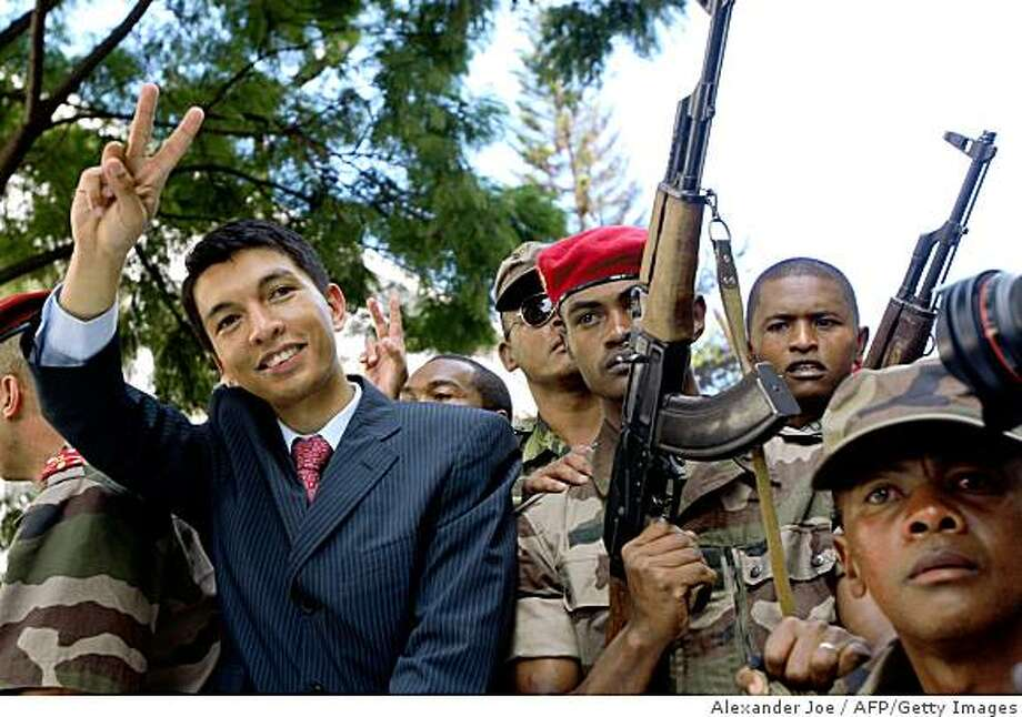 Madagascar opposition leader Andry Rajoelina (C) gives the V for victory sign as he parades through the streets of Antananarivo on March 17, 2009. Madagascar President Marc Ravalomanana resigned today, diplomats said, bowing to the inevitable after the army blasted its way into his offices and let the opposition leader take control.AFP PHOTO/ALEXANDER JOE (Photo credit should read ALEXANDER JOE/AFP/Getty Images) Photo: Alexander Joe, AFP/Getty Images