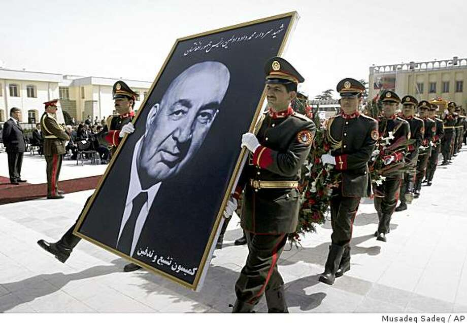Afghan guards of honor carry a portrait of Afghanistan's first President Mohammed Daoud during a ceremony to rebury him at the presidential palace in Kabul, Afghanistan, Tuesday, March 17, 2009. Daoud's remains along with his aides were recently discovered at a mass grave after they were shot dead during a military coup in the presidential palace in 1978 and replaced by Afghanistan's first communist ruler, Nur Mohammed Taraki. (AP Photo/Musadeq Sadeq) Photo: Musadeq Sadeq, AP