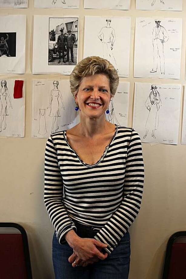 The Tosca Project co-creator and A.C.T. artistic director Carey Perloff in front of examples of the costume design for the show by Robert de La Rose at ACT's studio in San Francisco, Calif., on Friday, May 21, 2010.  .  Costume sketches made by Taisia Nikonishenko. Photo: Liz Hafalia, The Chronicle