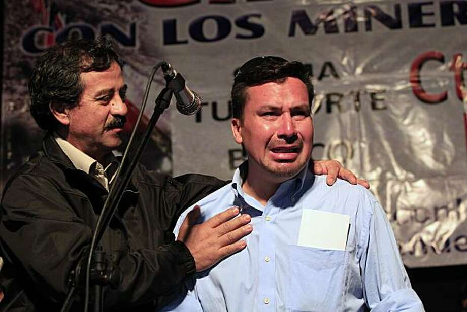 This Oct. 19, 2010, file photo shows rescued miner Edison Pena, right, crying while fellow rescued miner Juan Illanes supports him during a ceremony honoring the miners in Caldera, Chile.  New York Road Runners president Mary Wittenberg says Pena has sent word through the Chilean consulate that he wants to run in Sunday's, Nov. 7, 2010,  NYC marathon. Pena is one of 33 miners who were trapped for 69 days after an Aug. 5 collapse stranded them nearly a half-mile underground. Pena jogged regularly inthe unblocked tunnels, and marathon officials invited him to participate in the race after hearing his story. Photo: Martin Mejia, AP