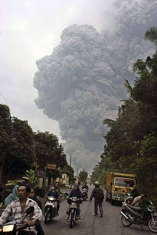 Residents flee on their motorcycles as Mount Merapi releases pyroclastic flow as seen from Klaten, Central Java, Indonesia, Sunday, Oct. 31, 2010. The deadly volcano spewed searing cloud of ash down its slopes Sunday, prompting panic and chaos among thousands of villagers who had taken advantage of a lull in activity to rush home and check on their livestock. Photo: AP