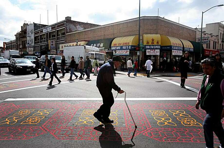 A man crosses the street in the Chinatown district in Oakland, Calif. on Tuesday,  March 17, 2009 Photo: Mark Costantini, The Chronicle