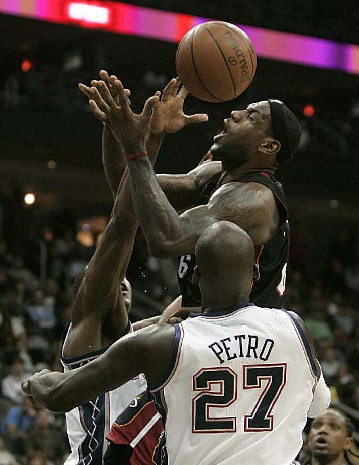 Miami Heat's LeBron James (6), is fouled by New Jersey Nets' Derrick Favors, left, as Nets' Johan Petro (27), of France, looks on in the third quarter during an NBA basketball game in Newark, N.J., Sunday, Oct. 31, 2010. The Heat defeated the Nets 101-78. Photo: Rich Schultz, AP