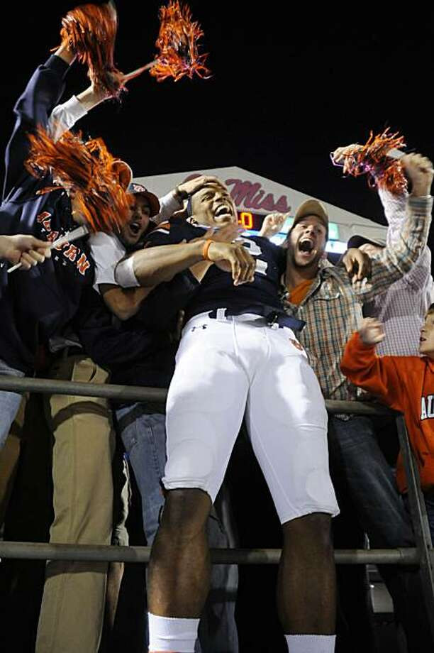 Auburn quarterback Cam Newton (2) is swamped by fans following their 51-31 win over Mississippi in an NCAA college football game in Oxford, Miss., Saturday, Oct. 30, 2010. Photo: Austin McAfee, AP