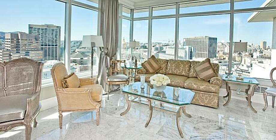 """An interior image from ShowRise decorating event at the SOMA Grand in San Francisco. """"The furniture is low so it doesn't interfere with the spectacular views,"""" says Azouaou of the main penthouse living room. Glass tabletops show off the white Carrara marble floors.A crystal chandelier and matching lamps from The Sherill Collection complete the look   Proceeds of event to benefit the San Francisco Lighthouse.  Sophie Azouaou, owner of SophiSticate Spaces with the help of the design community, designed penthouses at the Soma Grand. Located in the heart of SOMA, The Soma Grand is one of the newest highrises in San Francisco. Photo: Moanalani Jeffrey"""