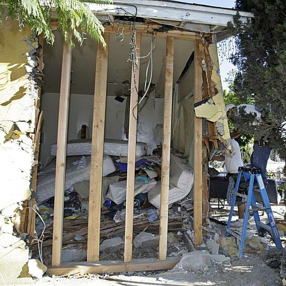 Mattresses and other items are seen in the corner bedroom of a home, as workers shore up the structure, right, after 21-year-old Eduardo Villareal drove his Cadillac Escalade into the bedroom where his 19-year-old girlfriend and their 10-day-old infant were sleeping, in the Boyle Heights district of Los Angeles Monday, Nov. 1, 2010.  The woman and the baby died in the crash late Sunday, Oct. 31. Villareal was injured and will be booked for murder, police said. Photo: Reed Saxon, AP