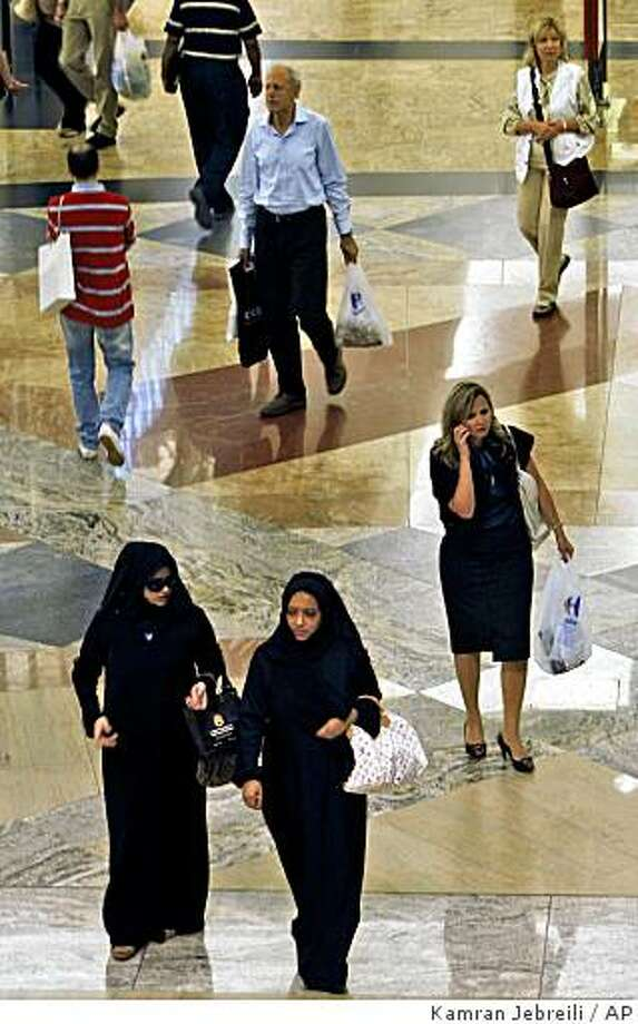 Two Emirati women walk next to a western woman at a shopping mall in Dubai, United Arab Emirates, Sunday, March 15, 2009. Dubai authorities are contemplating tougher penalties  for what they deem inappropriate behavior and plan to enforce a stricter dress code for foreign visitors to this glitzy Gulf city-state, that sells itself to the West as a party hot spot, although its Arab population hews to conservative Muslim values. (AP Photo/Kamran Jebreili) Photo: Kamran Jebreili, AP