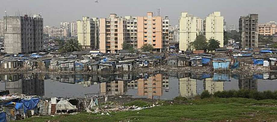 ** ADVANCE FOR USE ON SUNDAY, OCT. 31, 2010 AND THEREAFTER ** This Oct. 19, 2010 photo shows tall buildings behind  makeshift houses in the Rafiq Nagar slum in Mumbai, India. When U.S. President Barack Obama visits India Nov. 6, 2010, he will find a country of startlingly uneven development and perplexing disparities, where more people have cell phones than access to a toilet, according to the United Nations. Photo: Rafiq Maqbool, AP