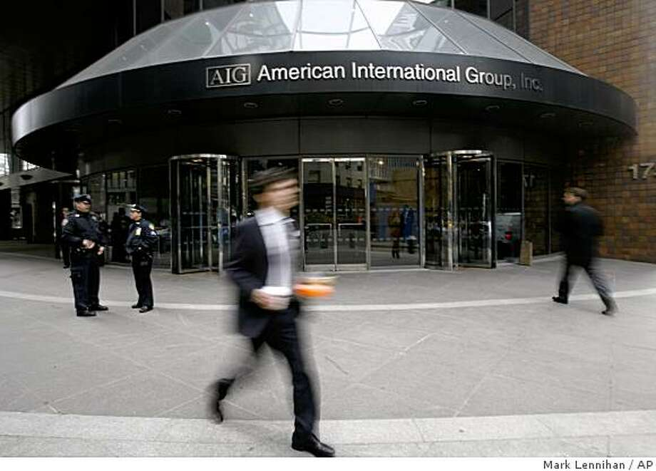 A man passes an AIG office building Monday, March 16, 2009 in New York.  American International Group Inc. used more than $90 billion in federal aid to pay out foreign and domestic banks, some of whom had received their own multibillion-dollar U.S. government bailouts. (AP Photo/Mark Lennihan) Photo: Mark Lennihan, AP