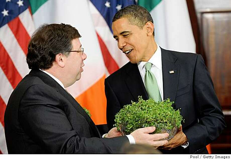 WASHINGTON - MARCH 17:  (AFP OUT) U.S. President Barack Obama (R) is presented with a bowl of shamrock by Irish Taoiseach Brian Cowen (L) during the annual shamrock ceremony at the White House March 17, 2009 in Washington, DC. Cowen was in Washington for St. Patrick?s Day celebrations.   (Photo by Matthew Cavanaugh-Pool/Getty Images) Photo: Pool, Getty Images