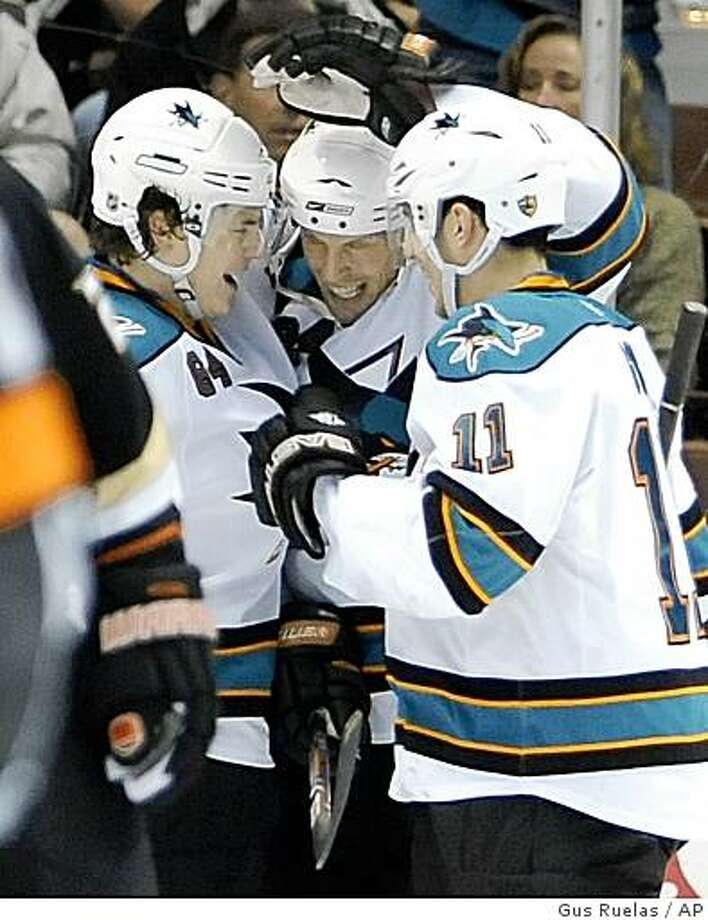 San Jose Sharks left wing Jamie McGinn (64) and San Jose Sharks center Marcel Goc (11), of Germany, celebrate teammate left wing Travis Moen's goal during the second period of an NHL hockey game, Sunday, March 15, 2009, in Anaheim, Calif. (AP Photo/Gus Ruelas) Photo: Gus Ruelas, AP