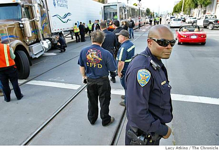 San Francisco Police direct traffic along Third Street, where a 18-wheel truck and a Muni train collided and sent seven T-Third passengers to the hospital. Photo: Lacy Atkins, The Chronicle