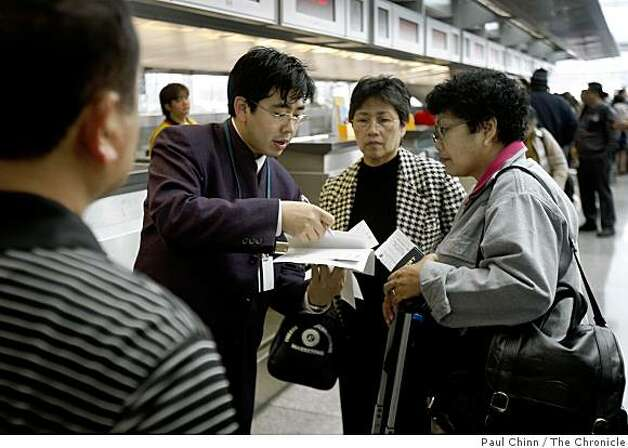 Benny Li (second from left) issues boarding passes to Lydia Tiquia (center) and her sister Estrellita Mardicas (right) before their flight to the Philippines at San Francisco International Airport in San Francisco, Calif., on Tuesday, March 17, 2009. Mardicas' husband Ed (far left), who is also traveling on the family's three-week vacation, purchased the tickets two months ago when fares were high but said he's noticed a lot of package deals and incentives offered by the airlines lately. Photo: Paul Chinn, The Chronicle