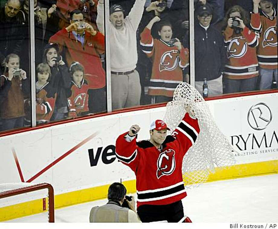 New Jersey Devils goalie Martin Brodeur holds up a puck and the net after the Devils beat the Chicago Blackhawks 3-2 in an NHL hockey game Tuesday, March 17, 2009 in Newark, N.J. Brodeur set the record for most wins by a goaltender with 552. (AP Photo/Bill Kostroun) Photo: Bill Kostroun, AP