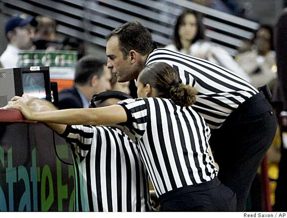 Officials view the final play of the game before determining that a basket made by California with three-tenths of a second left did not beat the buzzer, resulting in a 69-67 loss to Southern California in an NCAA semifinal college basketball game in the Pac-10 women's tournament in Los Angeles Saturday, March 14, 2009.  (AP Photo/Reed Saxon) Photo: Reed Saxon, AP