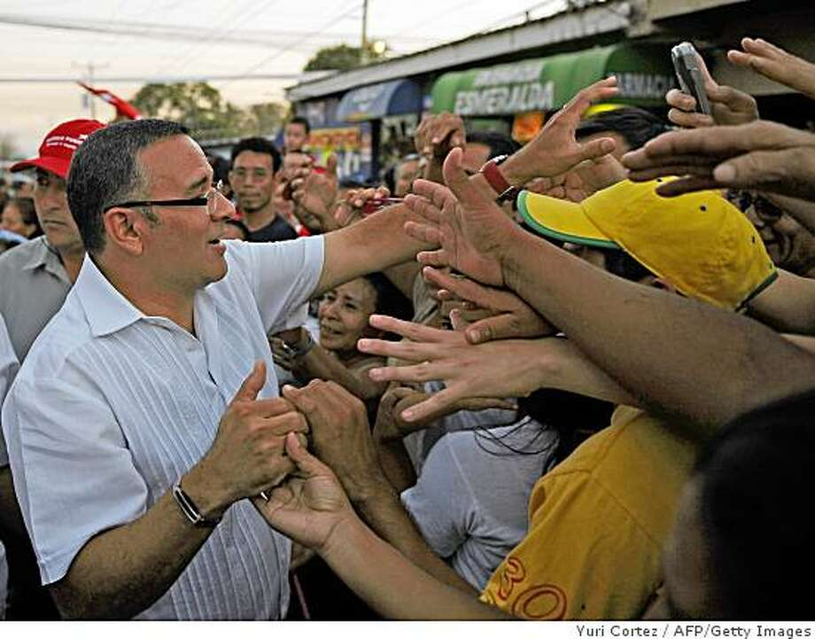 The presidential candidate of the Farabundo Marti National Liberation Front (FMLN) Mauricio Funes (L) shakes hands with some of his supporters during an election campaign closing rally in Zaragoza, some 25 kilometers south of the capital on March 9, 2009. Salvadoreans return to the polls on March 15 to elect a new president for the next five years.  AFP  PHOTO/ Yuri CORTEZ (Photo credit should read YURI CORTEZ/AFP/Getty Images) Photo: Yuri Cortez, AFP/Getty Images