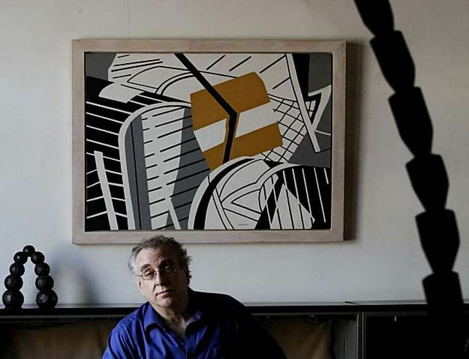 """In this Oct. 8, 2010 photo, framed by his own sculptures, """"Arch of Sphere,"""" left, and """"Tower 2,"""" right, artist sculptor John Crawford sits in his living room in the foreground of his father's abstract painting """"St. Gilles,"""" in Brooklyn, New York.  Crawford reclaimed art created by his father off the gallery walls of convicted art swindler Lawrence Salander. Photo: Bebeto Matthews, AP"""