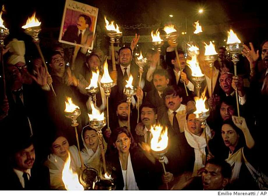 Pakistani lawyers hold candles as they shout anti-government slogans during a demonstration next to the High Court of Lahore, Pakistan, Saturday, March 14, 2009. Pakistan's government put the army on alert ahead of planned opposition protests in the capital, the military said Saturday, as the U.S. called for talks to end a crisis endangering the country's efforts against Islamist extremism. (AP Photo/Emilio Morenatti) Photo: Emilio Morenatti, AP