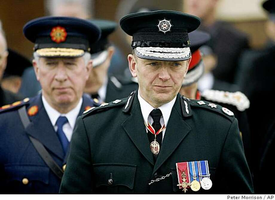 Chief Constable of the Police Service of Northern Ireland Hugh Orde, right, and Garda Commissioner Fachtna Murphy walk behind the coffin of Constable Stephen Carroll at St Therese's Roman Catholic church in Banbridge, Northern Ireland, Friday, March, 13, 2009. Constable Carroll, 48, was shot by Irish Republican dissidents while on duty in Craigavon on Monday. Thousands of people lined the streets outside St Therese Church in his hometown of Banbridge, County Down, where funeral mass was held. (AP Photo/Peter Morrison) Photo: Peter Morrison, AP