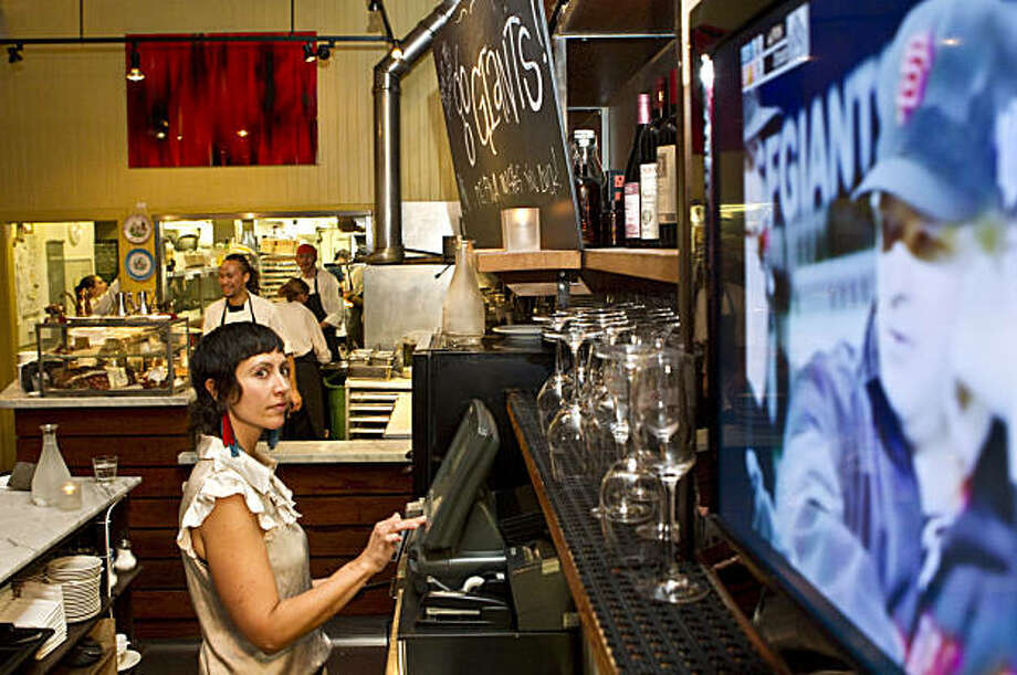 Jeanine Gade keeps her eye on the Giants game while working at Delfina in San Francisco, Calif., on Thursday, October 28, 2010.  Normally the restaurant doesn't have a television, but the owner Craig Stoll had one brought into the bar so diners can watch the games. Photo: Laura Morton, Special To The Chronicle