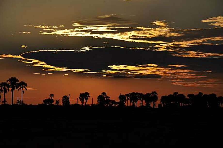 Sunset ignites the African skies above the shores of Botswana's remote and mysterious Makgadikgadi. Photo: Mark Sissons, Special To The Chronicle