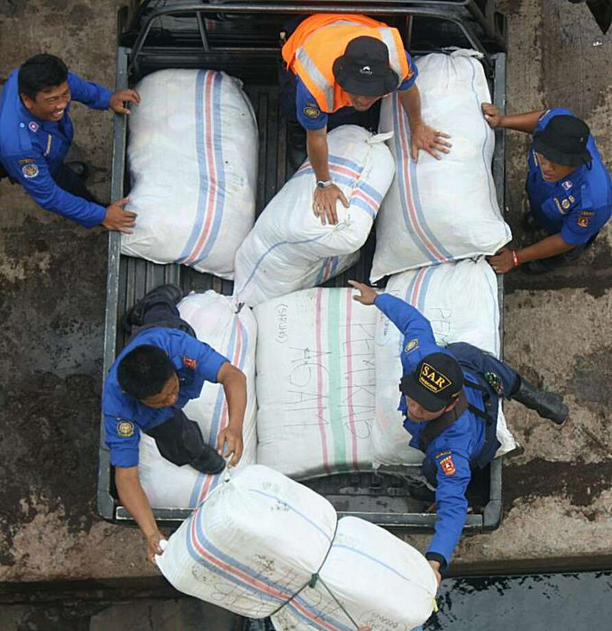 Workers load relief goods for tsunami victims in the Mentawai islands onto a supply ship at the port of Padang, in West Sumatra, on October 29, 2010.  Indonesia battled to deliver aid to remote islands where the tsunami has killed over 400 people, as bodies lay strewn on beaches and buried in debris days after the wave hit. Photo: Rus Akbar, AFP/Getty Images