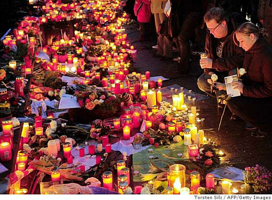 Mourners light a candle next to a sea of flowers and candles left by residents on March 12, 2009  in Winnenden, southern Germany, one day after a teenager in black combat gear went on the rampage at his former school, the Albertville secondary school, killing 15 people before fleeing and sparking a major manhunt. The 17-year-old had announced his intentions in an Internet chatroom less than seven hours earlier. Photo: Torsten Silz, AFP/Getty Images