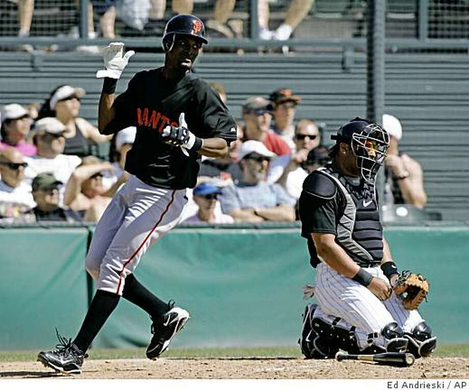 ** RETRANSMISSION OF AZEA105 FOR ALTERNATE CROP ** San Francisco Giants Eugenio Velez, left, celebrates as he scores from third on a triple by teammate Fred Lewis in the second inning during a spring training baseball game against the Colorado Rockies in Tucson, Ariz., Friday, March 13, 2009.  Rockies catcher Yorvit Torrealba is pictured at right. (AP Photo/Ed Andrieski) Photo: Ed Andrieski, AP