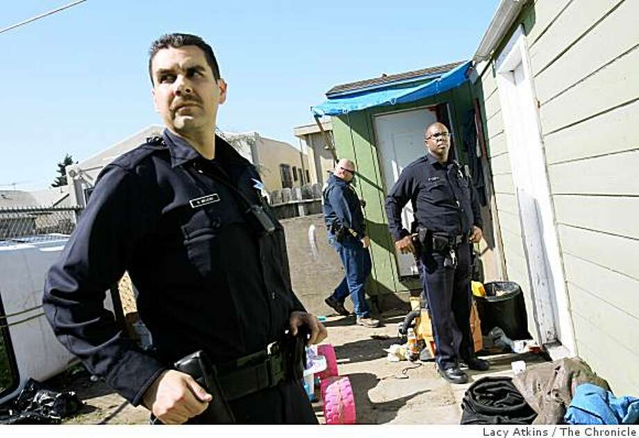 Officer Geraldo Melero (right) and other members of the Oakland Police Department respond to a call about people smoking Methamphetamine in a garage on Thursday March 12,  2009, in Oakland, Calif. Because of strong police presence the violent crime in Oakland is down 23 percent in the first quarter of 2009 compared with the same period last year. Photo: Lacy Atkins, The Chronicle