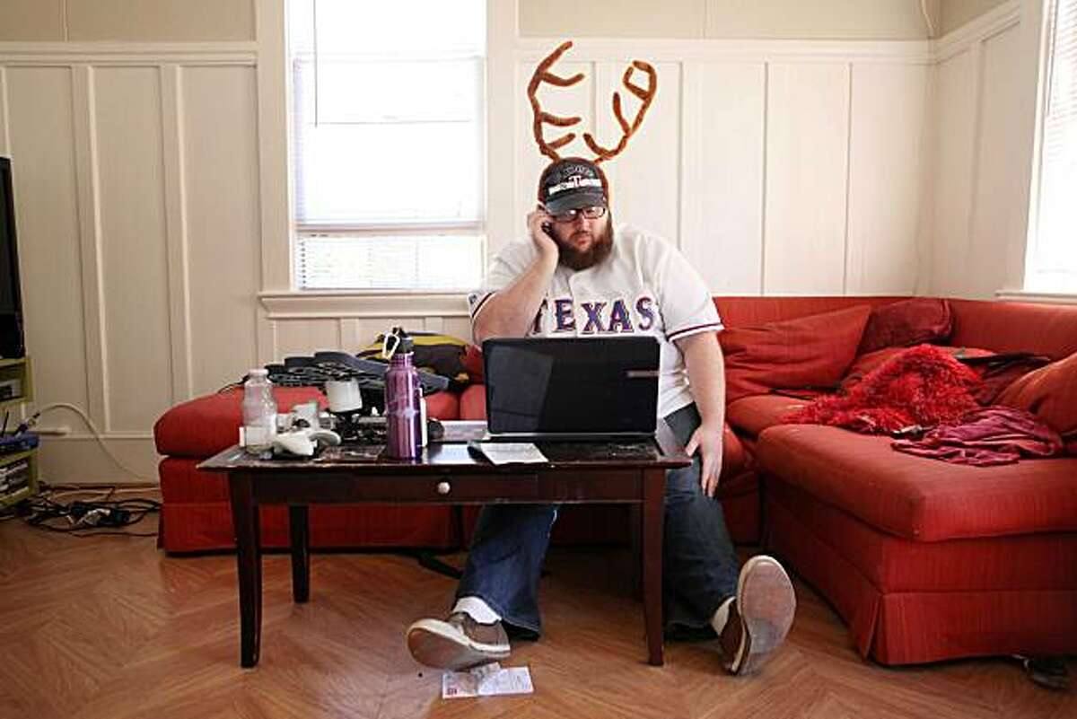 """Wearing a $12 pair of antlers he found on Ebay and a his prized Texas Rangers jersey, Christopher Fittz, professed Rangers fan living in a sea of Giants, agonizes over trying to find World Series tickets with a friend on the phone in his living room on Tuesday Oct. 26, 2010 in Emeryville, Calif. Prepared to spend 600 0r 700 dollars for a ticket he said, """"Money comes and goes but this is a once in a lifetime thing."""""""