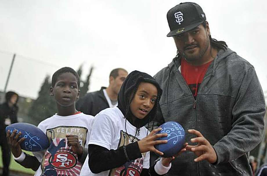Guard of the San Francisco 49ers American Football club, Mike Iupati, right, coaches school kids during the NFL Football And Football community coaching clinic in London, Tuesday, Oct. 26, 2010. Photo: Lennart Preiss, AP
