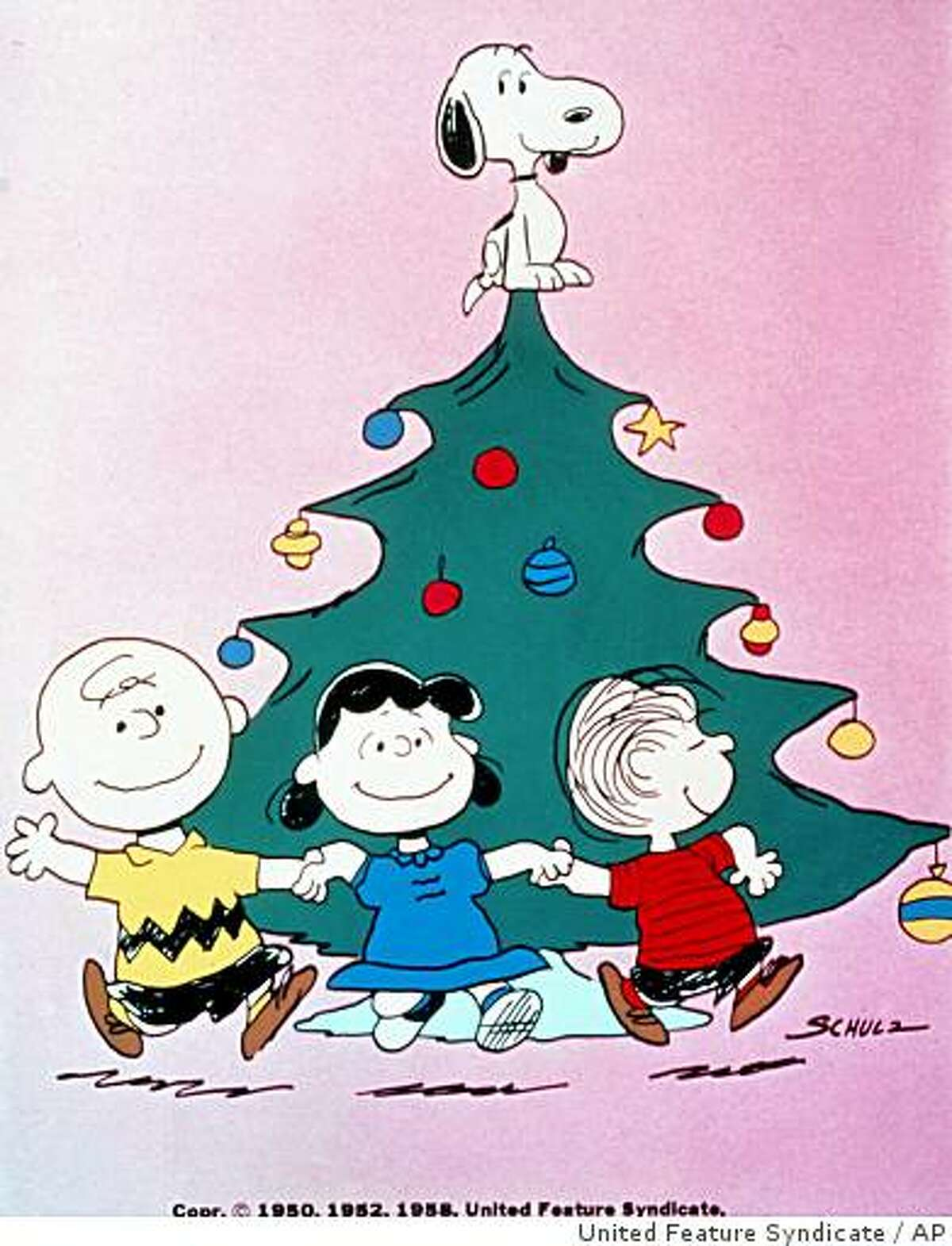 With Snoopy atop the tree, Charlie Brown, Lucy and Linus celebrate the holiday season in