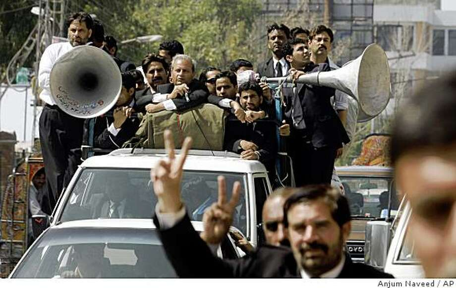 Pakistani lawyers march in a road during a demonstration for the reinstatement of  deposed Chief Justice Iftikhar Mahmood Chaudhry in Rawalpindi, Pakistan Wednesday, March 11, 2009. Pakistan banned protests in two provinces and arrested scores of lawyers and opposition leaders Wednesday ahead of planned rallies threatening to batter the already-shaky rule of its pro-Western government. (AP Photo/Anjum Naveed) Photo: Anjum Naveed, AP