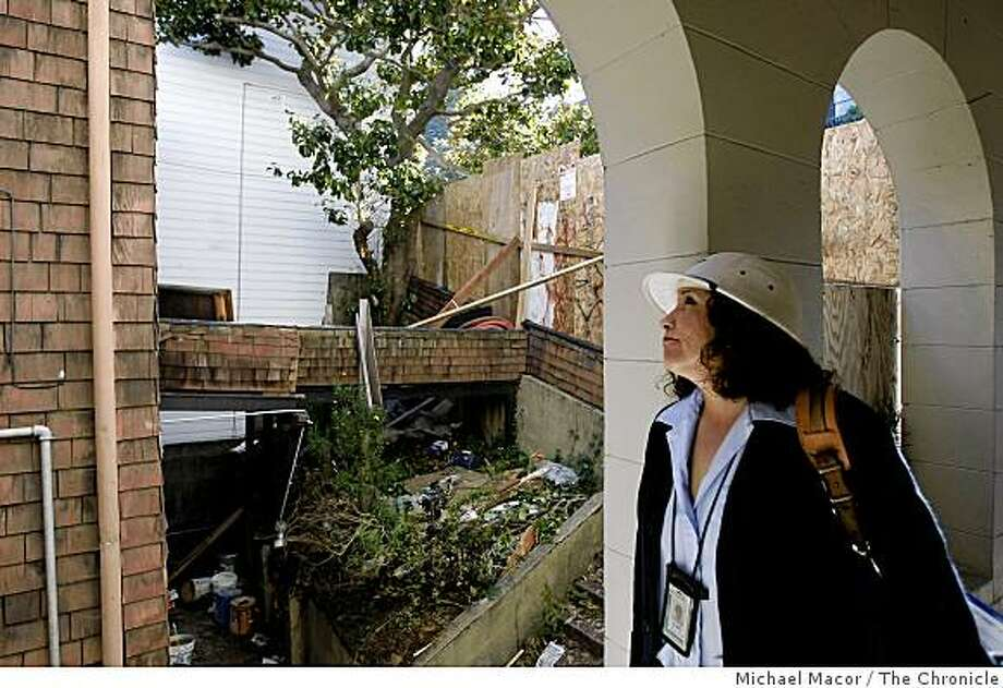 Letter carrier Alma Silva-Orden surveys the home at 1268 Lombard Street on Wednesday, March 11, 2009 in San Francisco, Calif. Preservationists are currently trying to convince the City of San Francisco not to demolish the 1861 home. The city attorney's office has opened an investigation into whether the owner willfully neglected the building at 1268 Lombard St. to skirt rules intended to protect historic structures. Photo: Michael Macor, The Chronicle
