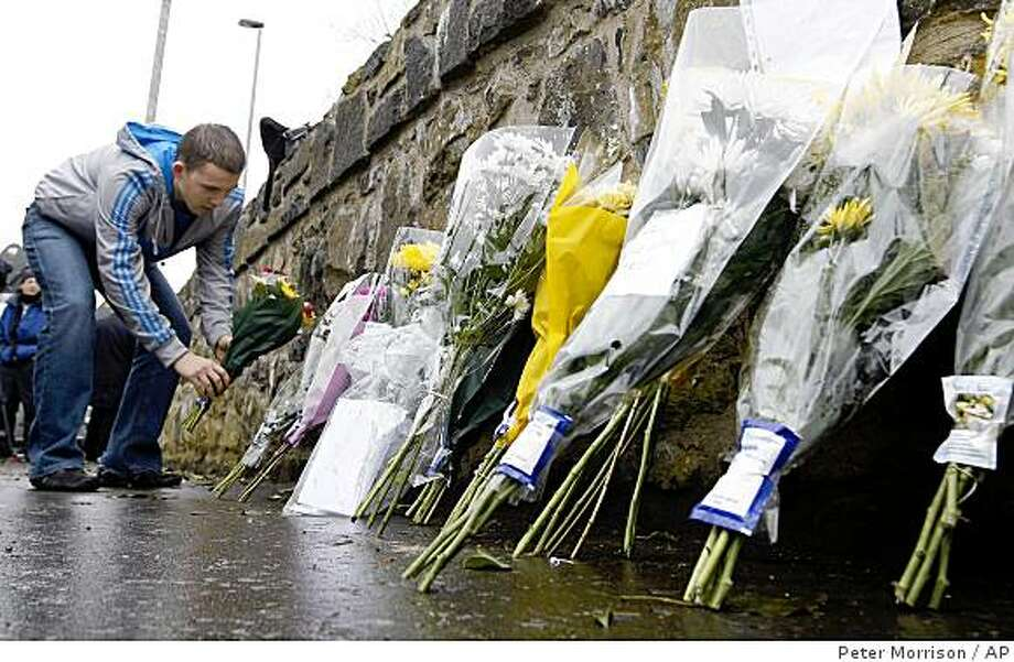 A man leaves flowers near Massereene army barracks, in Antrim, west of Belfast, Northern Ireland, Sunday, March, 8, 2009. Suspected IRA dissidents opened fire on British troops and pizza delivery men outside a Northern Ireland army base, killing two soldiers and wounding four other people. Police said Sunday the attackers fired on their victims again as they lay wounded on the ground. (AP Photo/Peter Morrison) Photo: Peter Morrison, AP