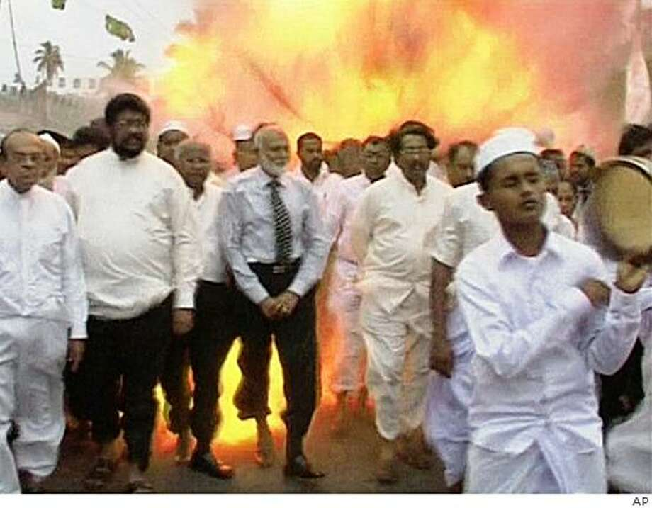 This image made from video shows an explosion in background, as Sri Lankan Muslim men perform during a religious procession in Akuressa, in Matara, about 160 kilometers (100 miles) south of Colombo, Sri Lanka, Tuesday, March 10, 2009. A suicide bomber attacked a gathering of Muslims celebrating a religious holiday in southern Sri Lanka on Tuesday, killing 10 people and critically wounding a government minister, officials said. (AP Photo/APTN) Photo: AP