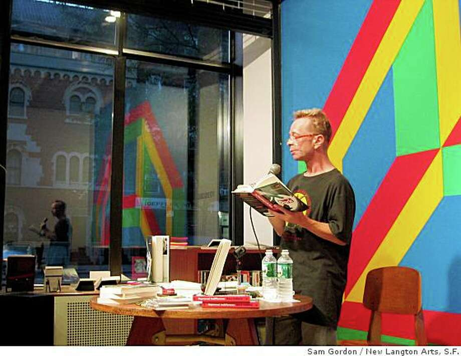 """frame from """"The Lost Kinetic World, Volume One"""" (2005) video by Sam Gordon.Frame shows Gary Indiana reading aloud in front of a Sol LeWitt wall drawing. Photo: Sam Gordon, New Langton Arts, S.F."""