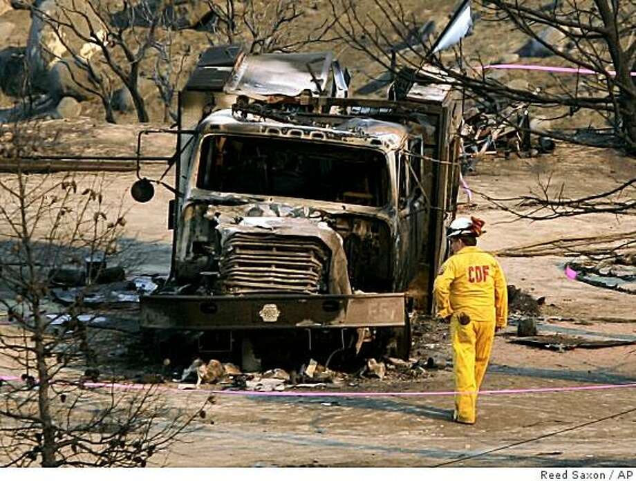 firefighter from the California Department of Forestry examines the burned-out crew transport rig where four firefighters died and one was seriously burned fighting the Esperanza fire in Twin Pines, Calif., Friday, Oct. 27, 2006. Photo: Reed Saxon, AP