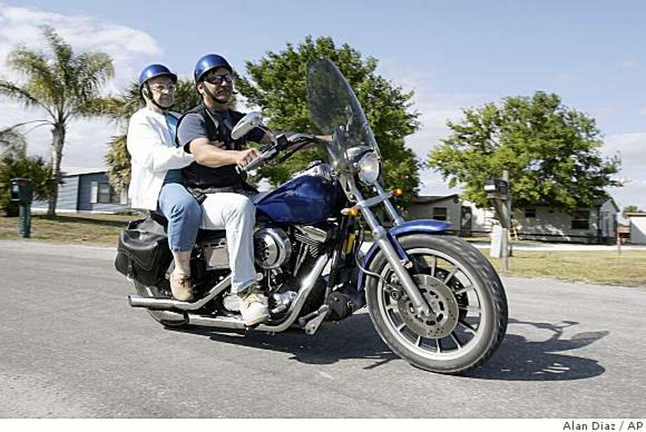 June Pearce, 84, rides on the back of Ron Borowski's motorcycle in Okeechobee, Fla., March 6, 2009. Ron gave June a ride on his bike as a surprise birthday present. (AP Photo/Alan Diaz) Photo: Alan Diaz, AP