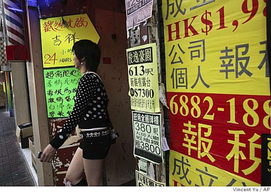 "**APN ADVANCE FOR MARCH 8**  A woman walks by hand-written signs advertising a prostitution service near the entrance of an apartment building in Hong Kong's Mong Kok shopping district Thursday, Feb. 12, 2009. The recent killings of four ""phoenix sisters"" in Hong Kong, as prostitutes are known locally, shocked locals and sparked fears of a serial killer. Police quickly arrested and charged a 24-year-old man with two of the murders. (AP Photo/Vincent Yu) Photo: Vincent Yu, AP"