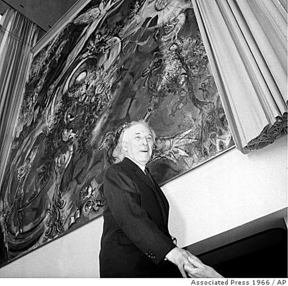 """In this file photo of Sept. 8, 1966, Marc Chagall poses by his mural """"Le Triumphe de la Musique,"""" The Triumph of Music, during the unveiling ceremonies in the lobby of the Metropolitan Opera House at Lincoln Center, New York. The Metropolitan Opera has put up two giant Chagall murals in its lobby as collateral on a loan, the latest sign of how the nation's top fine arts institutions are struggling to cope with the economic downturn. With stock portfolios plummeting and the economy tanking, owners of expensive art are increasingly putting up their collections as collateral to obtain a much-needed infusion of cash.  (AP Photo, File) Photo: Associated Press 1966, AP"""
