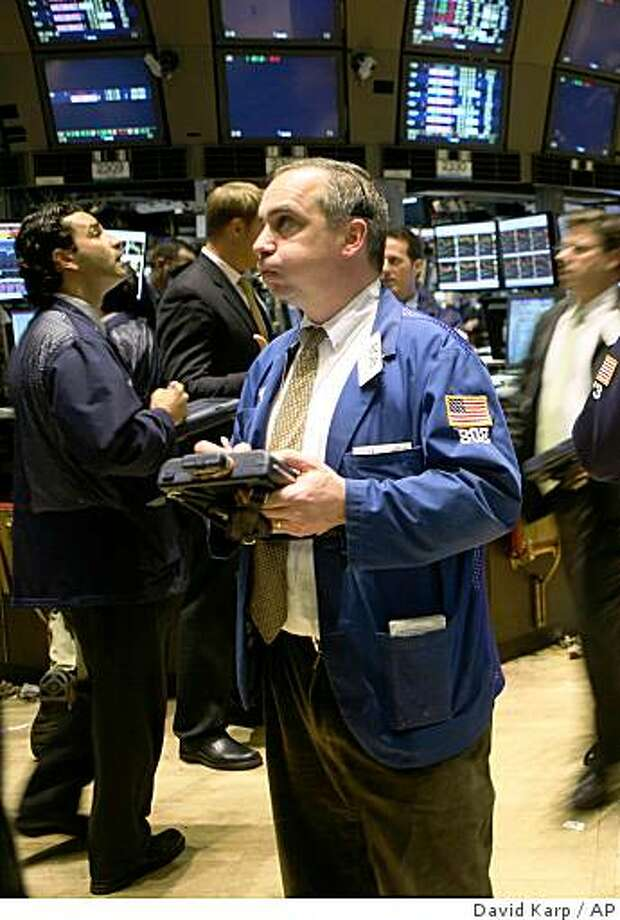 An unidentified trader monitors the scores as he works his post on the trading floor of the New York Stock Exchange just before the closing bell Thursday, March  5,  2009  (AP Photo/David Karp) Photo: David Karp, AP