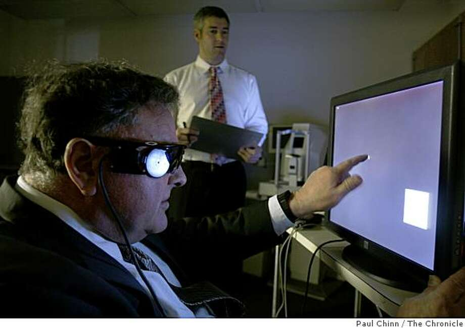 Dean Lloyd (left) uses a touch screen monitor to test his Argus II eye implant at UCSF Medical Center in San Francisco, Calif., on Friday, Feb. 27, 2009. Neuroscientist Matthew McMahon monitors Lloyd's progress. Lloyd, who has been completely blind for several years, can now see rough images of shapes and colors thanks to the experimental implant developed by Second Sight. Photo: Paul Chinn, The Chronicle