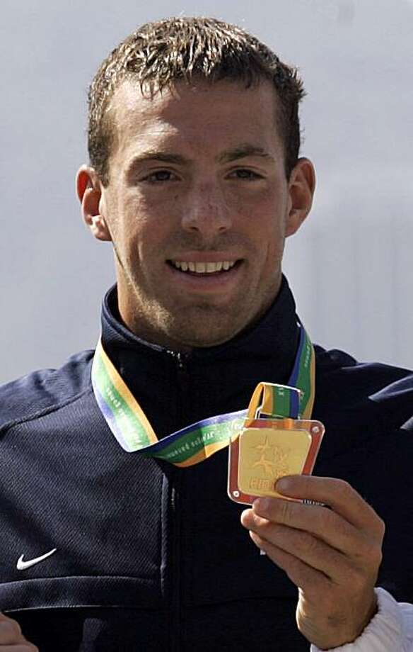 FILE - In this July 17, 2007, file phot,, Fran Crippen of the United States, holds up his goald medal he won in the men's 10-kilometer swimming marathon at the Pan American Games at Copacabana beach in Rio de Janeiro. Crippen died during a race in the United Arab Emirates on Saturday, Oct. 23, 2010. The 26-year-old swimmer from suburban Philadelphia was competing in the FINA Open Water 10-kilometer World Cup in Fujairah, south of Dubai, but failed to finish and was found in the water two hours later, according to Swimming World. Photo: Dario Lopez-Mills, Associated Press