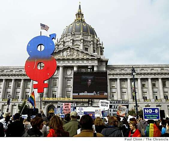 "A Proposition 8 supporter carries a large ""8"" through a crowd watching the state Supreme Court hearing on a big screen in front of San Francisco's City Hall. Photo: Paul Chinn, The Chronicle"
