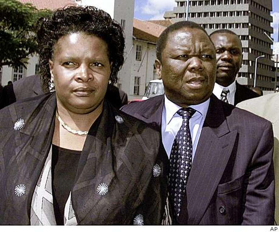 ** ADDS THAT SUSAN TSVANGIRAI WAS KILLED IN CAR CRASH  **  FILE  ** In this Monday, Feb. 3, 2003, file photo Morgan Tsvangirai, right, arrives at the Harare High Court, accompanied by his wife Susan, left.  Zimbabwean Prime Minister Morgan Tsvangirai was injured in a car crash on the outskirts of the capital Friday, March 6, 2009 and his wife was killed, officials said. Tsvangirai had been traveling to a weekend rally in the prime minister's home region, south of Harare, when their car sideswiped a truck, his spokesman James Maridadi said. No other details on the crash were immediately available.  (AP Photo/file) Photo: AP