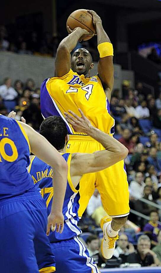 Los Angeles Lakers shooting guard Kobe Bryant, top, shoots as Golden State Warriors small forward Vladimir Radmanovic of Serbia defends during the first half of their NBA basketball game, Friday, Oct. 22, 2010, in Ontario, Calif. Photo: Mark J. Terrill, AP
