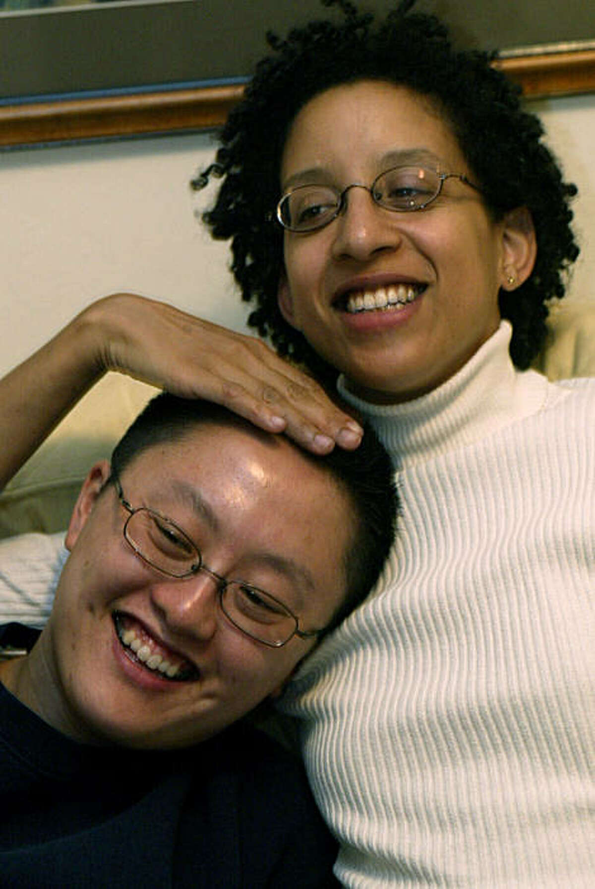 Amy Andre (right) a bi-sexual in a relationship with a strictly lesbian partner, Cheri Tsai (CQ), relax and watch television in their Chinatown apartment.