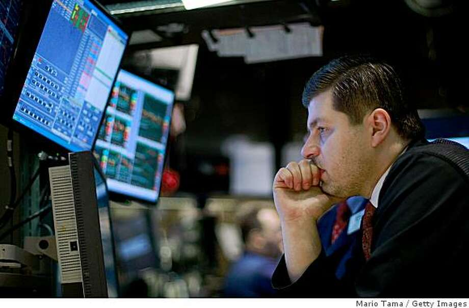 NEW YORK - MARCH 03:  A trader works on the floor of the New York Stock Exchange during morning trading March 3, 2009 in New York City. Stocks were mixed at the start of the day's trading as Federal Reserve Chairman Ben Bernanke told Congress an economic turnaround hinges on the government's success in stabilizing financial markets. Yesterday stocks closed at 6,763.29, noting it as first time the Dow Jones Industrial Average closed below 7,000 since May 1997.   (Photo by Mario Tama/Getty Images) Photo: Mario Tama, Getty Images
